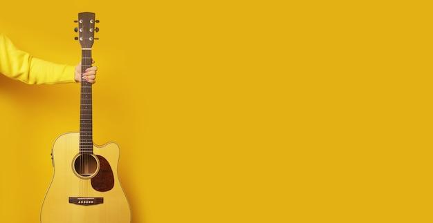 Guitarra na mão sobre a parede amarela,