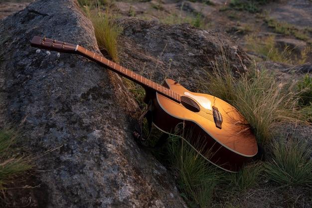 Guitarra na rocha. violão violão ao ar livre no pôr do sol, conceito de fundo de música. instrumento musical