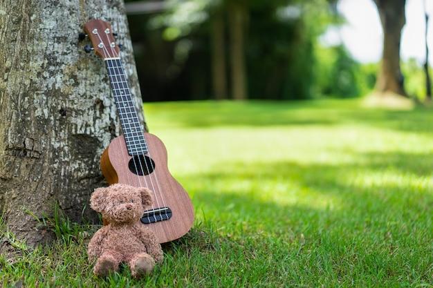Guitarra ukulele com boneco de urso sob a árvore em campo de grama verde com luz do sol