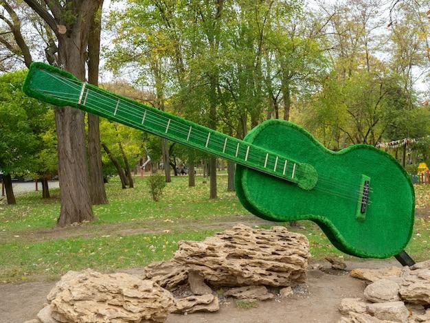 Guitarra verde decorativa no parque da cidade