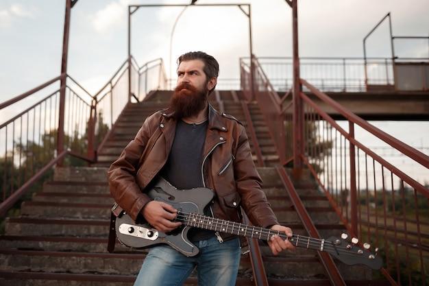 Guitarrista barbudo brutal de cabelos grisalhos, jaqueta de couro marrom e jeans azul segura uma guitarra elétrica preta e olha para longe