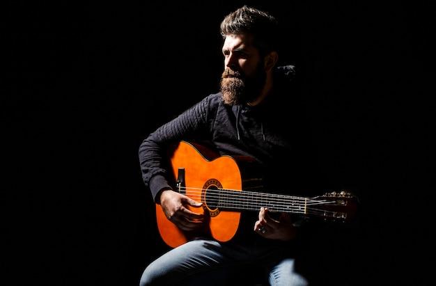 Guitarrista barbudo joga. tocar guitarra. homem de barba hipster sentado em um bar.