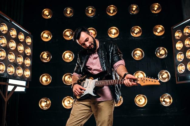 Guitarrista barbudo masculino em jaqueta de couro preta no palco com a decoração de luzes.
