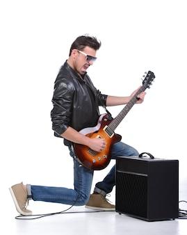 Guitarrista da rocha que joga a guitarra que está em um joelho.