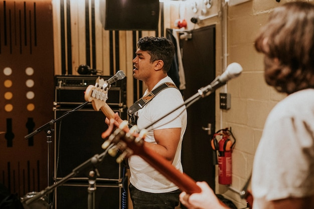 Guitarrista de banda de rock fazendo repetição em estúdio de gravação