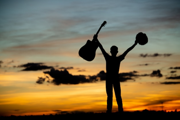 Guitarrista de garota de silhueta em um pôr do sol
