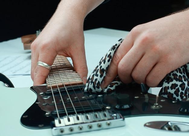 Guitarrista de rock, limpando o pescoço da guitarra