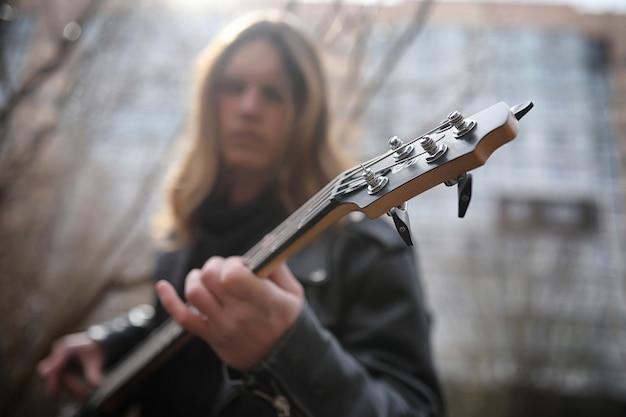 Guitarrista de rock nas escadas. um músico com um contrabaixo em um terno de couro. metalist com uma guitarra no fundo da etapa industrial.