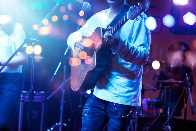 Guitarrista no estágio com iluminação para o blackground. guitarrista, macio e conceito do borrão.