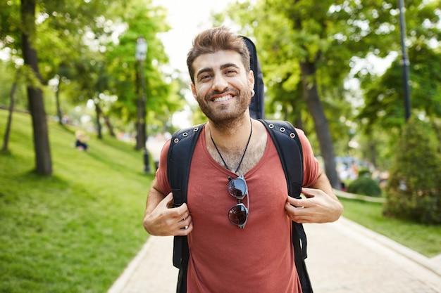 Guitarrista sorridente e despreocupado, cara com guitarra caminhando feliz no parque