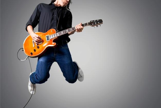 Guitarrista tocando música no fundo cinza da parede