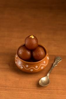 Gulab jamun em panela de barro com colher e frutos secos. sobremesa indiana ou prato doce