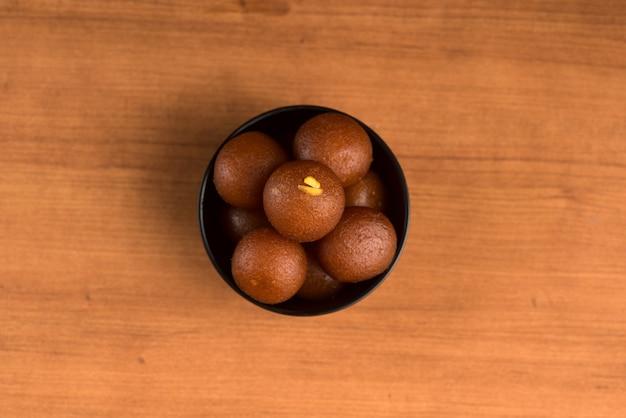 Gulab jamun em tigela com fundo de madeira.