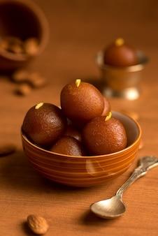 Gulab jamun em tigela e tigela de cobre antigo com colher. sobremesa indiana ou prato doce.