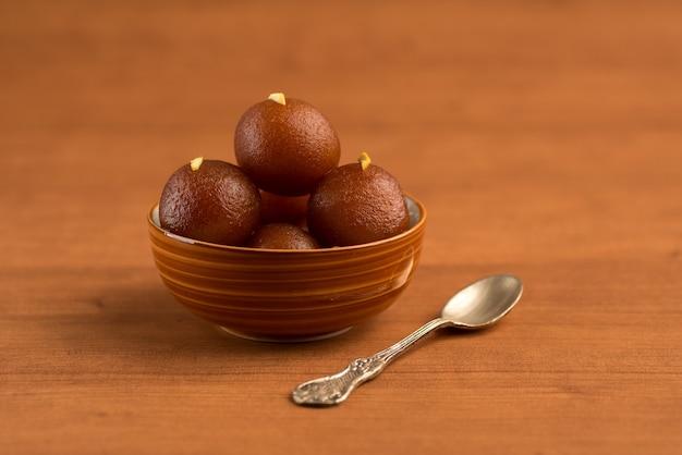 Gulab jamun em tigela na mesa de madeira. sobremesa indiana ou prato doce.