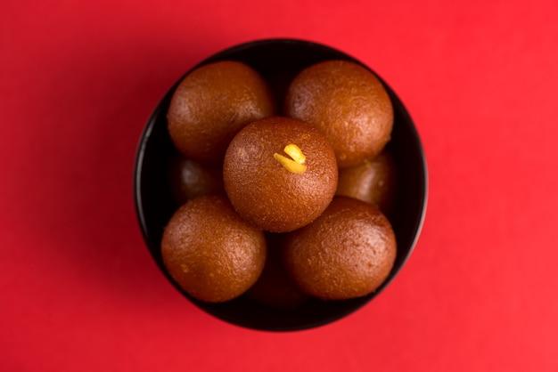 Gulab jamun em tigela preta sobre fundo vermelho. sobremesa indiana ou prato doce.