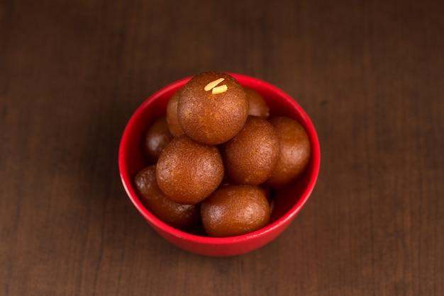 Gulab jamun em tigela vermelha em fundo de madeira. sobremesa indiana ou prato doce.