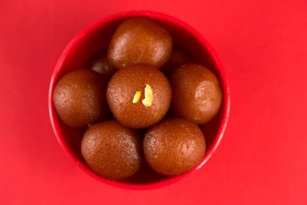 Gulab jamun em tigela vermelha sobre fundo vermelho. sobremesa indiana ou prato doce.