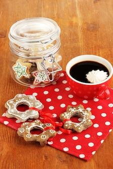 Guloseimas de natal e xícara de café em close-up de mesa de madeira