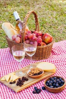 Guloseimas de piquenique de alto ângulo para dois com taças de vinho