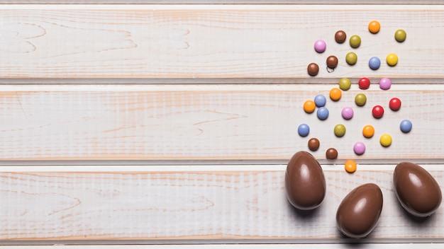 Guloseimas multicoloridas doces e três ovos de chocolate na superfície de madeira