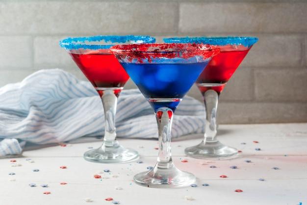 Guloseimas para o feriado do dia da independência em 4 de julho coquetéis caseiros com bebidas alcoólicas em cores tradicionais - vermelho azul branco com gelo na mesa da cozinha de casa
