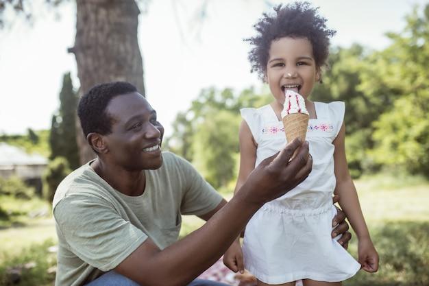 Guloso. garoto fofo de pele escura tomando sorvete e passando um tempo com o pai