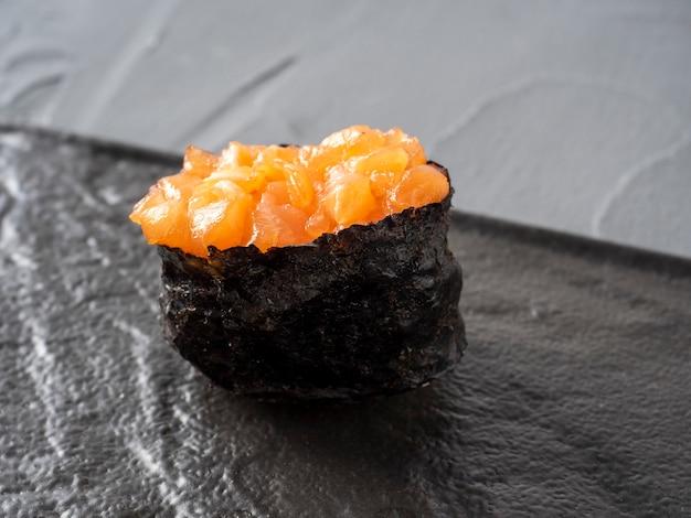 Guncan de salmão picado em uma superfície de textura preta. vista lateral de close-up. culinária japonesa