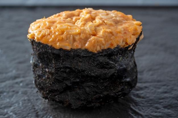 Guncan picante com frango e molho picante em uma superfície de textura escura. vista lateral