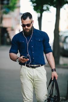 Guy caminha usando o seu celular