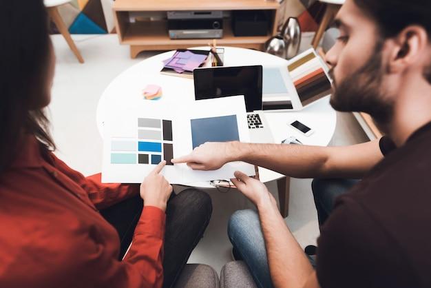 Guy e a garota escolhem as amostras de cores para o seu design.