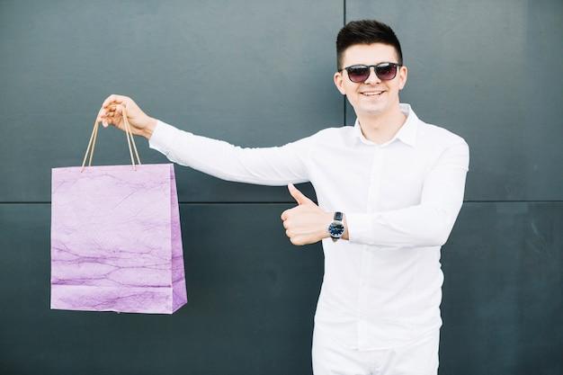 Guy em óculos de sol com saco de compras