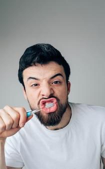 Guy limpando os dentes com força e concentrado. cuide da saúde com escova e creme dental. conceito de saúde
