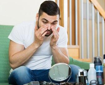 Guy olhando sua pele problemática em um espelho