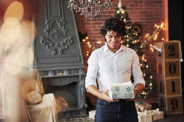 Guy pensa em quem ele dará esse presente. jovem de pé na bela sala decorada e segurando a caixa de presente branca na época do ano novo