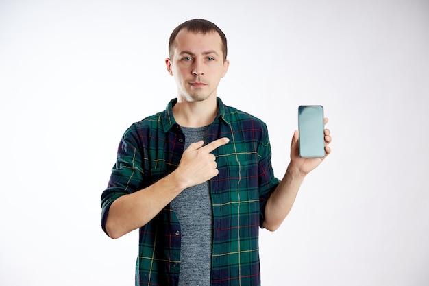 Guy segura o telefone nas mãos e aponta para ele com o dedo. um homem joga em seu telefone e assiste a vídeos, redes sociais