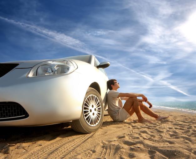 Guy sentado contra o carro esporte estacionado na praia