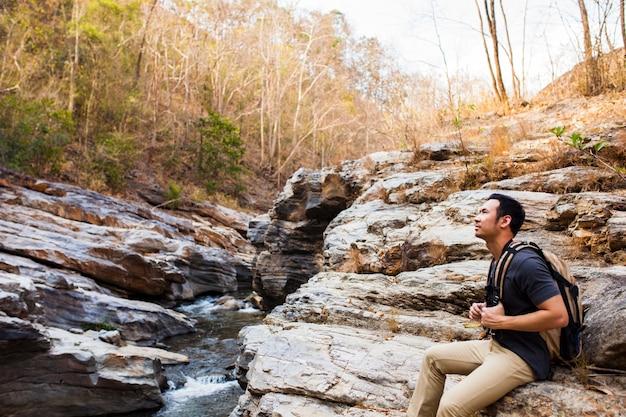 Guy sentado em rochas perto do rio