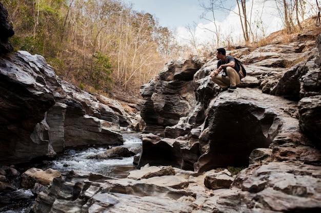 Guy sentado no rio selvagem