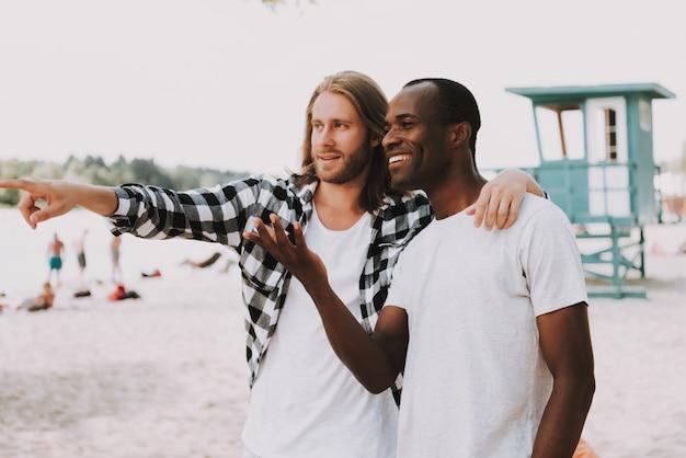 Guys abraço e apontando para o mar best friends travel