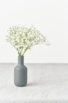 Gypsophila flores em um vaso. luz suave, minimalismo escandinavo, paredes brancas