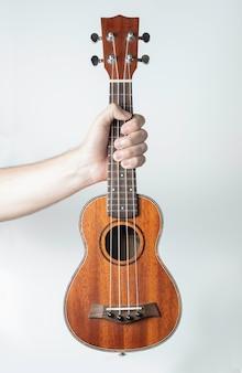 H pegando um ukulele de madeira. branco.