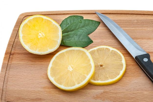 Há algumas fatias de limão e uma faca na tábua de corte.