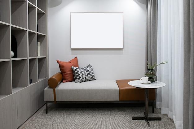 Há almofadas e cobertores no sofá da sala e molduras brancas na parede há espaço