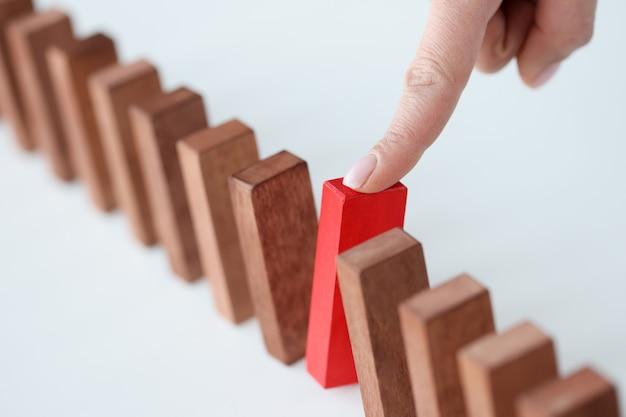 Há blocos de madeira na mesa, um deles em vermelho é puxado para fora, abordagem única para negócios