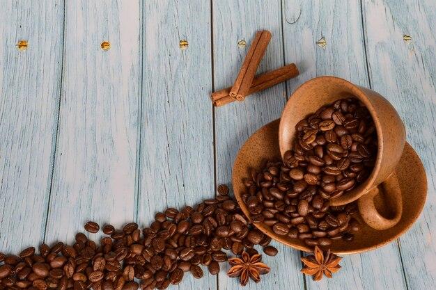 Há grãos de café na xícara e eles também estão espalhados pelo fundo de madeira
