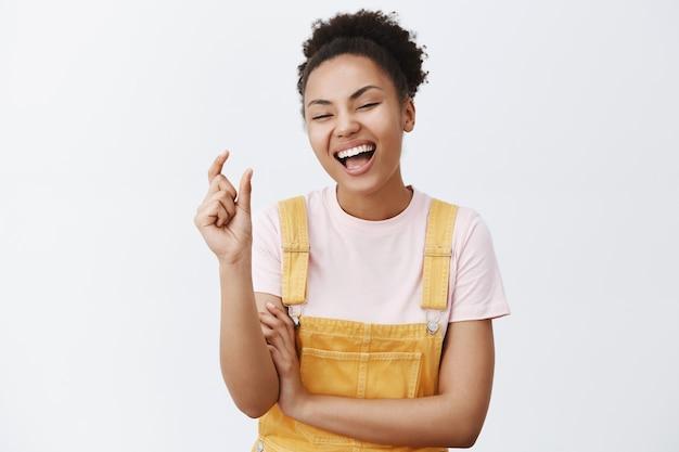 Ha-ha tão pequeno. retrato de uma jovem alegre e emotiva com pele escura e cabelos cacheados, modelando um objeto minúsculo e engraçado com os dedos, rindo alto, repreendendo alguém por causa do tamanho sobre uma parede cinza