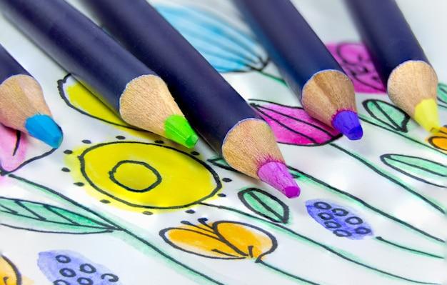 Há lápis aquarela multicoloridos na mesa ao lado de um desenho colorido