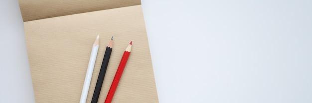 Há lápis vermelhos, brancos e pretos no caderno. conceito de aprendizagem de processos criativos