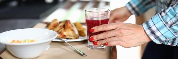 Há salada na bandeja e uma mão de mulher de segundo prato segura um copo com um líquido vermelho.
